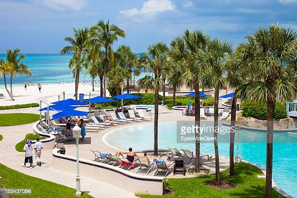 People are lying at a hotel pool close to the beach on June 15, 2012 in Nassau, The Bahamas.