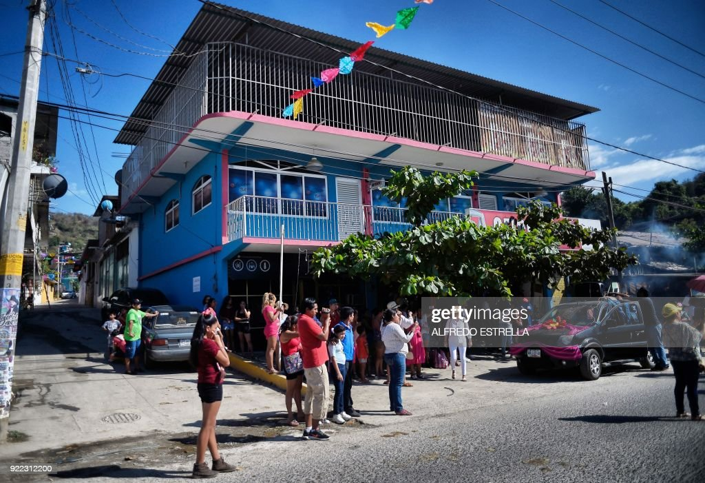 People are pictured in a street at Kilometro 30 community, near the Acapulco resort in Guerrero State, Mexico, on February 14, 2018. Violence in the state of Guerrero claimed the lives of two priests on February 5, 2018. / AFP PHOTO / Alfredo ESTRELLA / TO