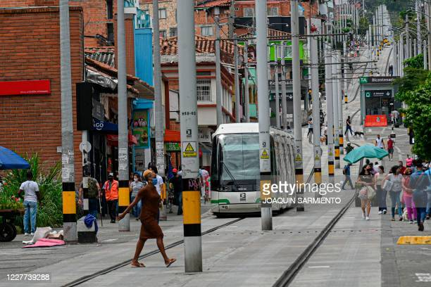 People are pictured on their daily life as the tram passes by in Medellin Colombia on July 22 2020 amid the COVID19 pandemic
