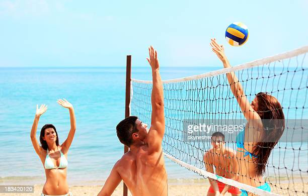 People are playing volleyball on the beach.