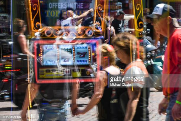 People are reflected in a casino window in downtown Deadwood South Dakota during the 80th Annual Sturgis Motorcycle Rally on August 8 2020 While the...