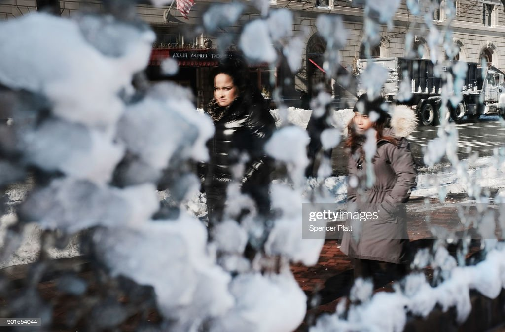 People are reflected in a frozen window the morning after a massive winter storm on January 5, 2018 in Boston, United States. Schools and businesses throughout the Boston area get back to work today after the city received over a foot of snow during a fast moving storm yesterday.