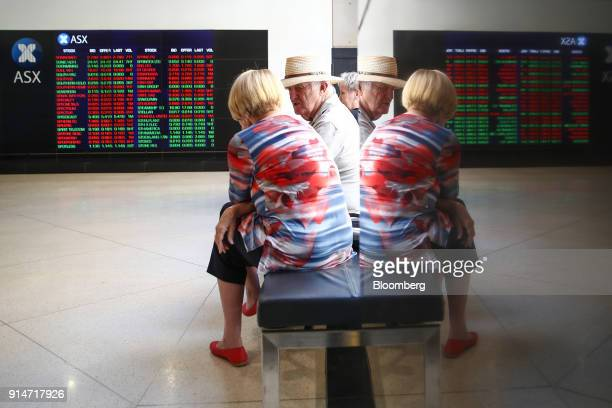 People are reflected in a glass while looking at electronic boards displaying stock information at the Australian Securities Exchange operated by ASX...