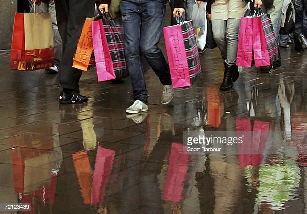 People are reflected in a puddle as they leave carrying shopping bags after shopping at a Topshop store on Oxford Street on October 6, 2006 in...