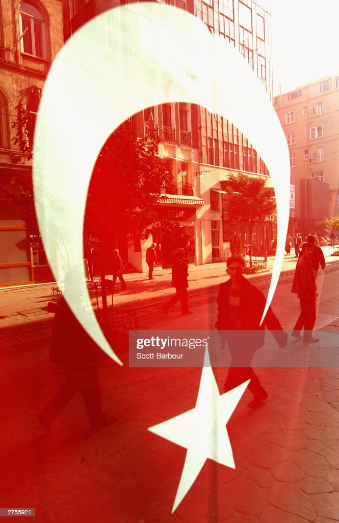 People are reflected in a shop window displaying the Turkish flag November 23, 2003 in Istanbul, Turkey. Daily life is returning to normal after bomb attacks on the British consulate and the HSBC bank headquarters killed 27 people and left hundreds injured last week.