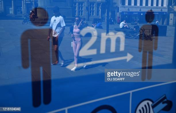 People are reflected in a sign advising the public to adhere to social distancing measures due to COVID19 in Durham north east England where 10...