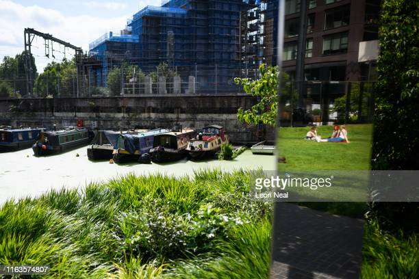 People are reflected in mirrored panels as they enjoy the sunshine at Gasholder Park on July 22 2019 in London England On July 22 London officially...