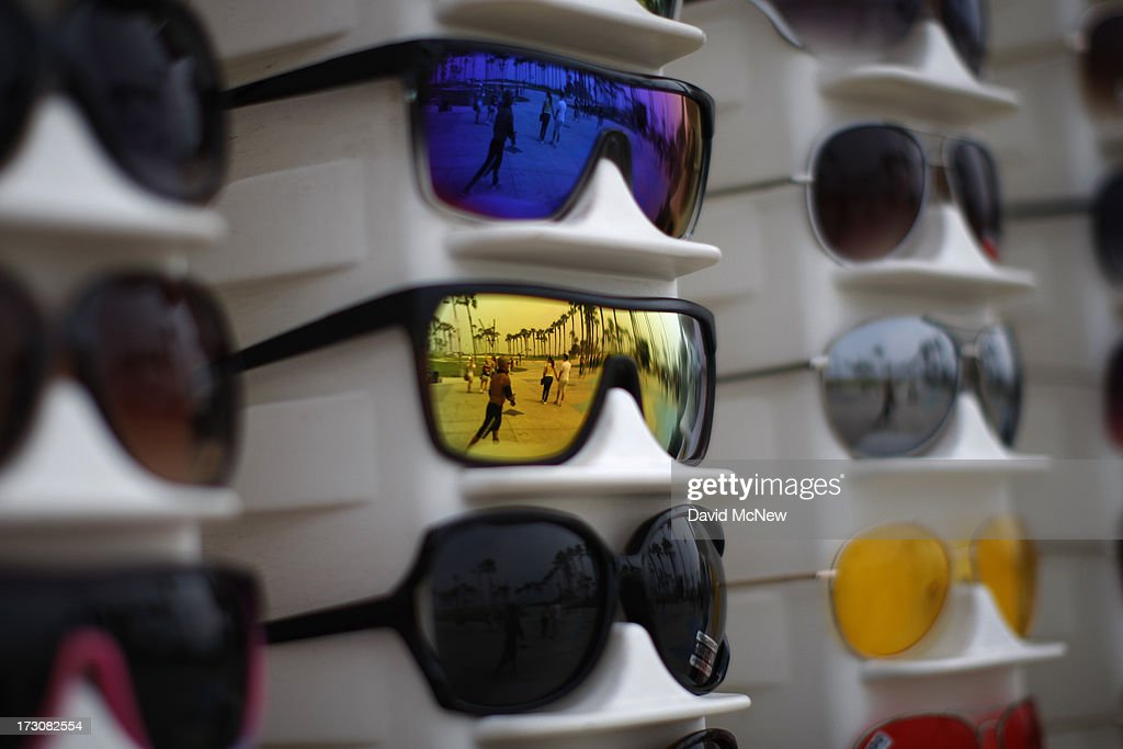 People are reflected in sunglasses for sale on the boardwalk on Independence Day weekend at Venice Beach on July 6, 2013 in Venice, California. An estimated 16 million people visit the famous beach city annually which is celebrating 108th birthday as of July 4.