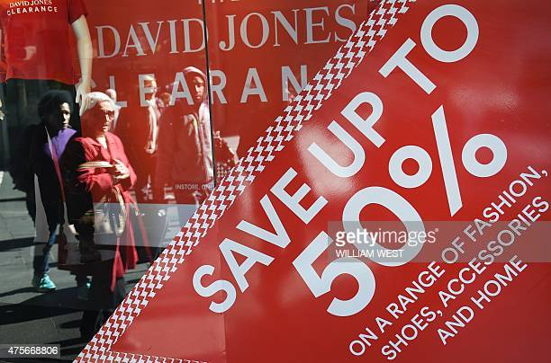 People are reflected in the shop window as the walk past sale signage in Sydney on June 3 with data showing Australia's economy was...