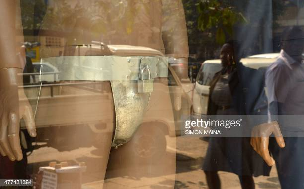 People are reflected in the window of a men's clothing shop next to a mannequin wearing a chastity belt with an iron padlock on sale for 20 USD on...