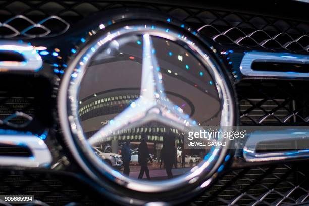 People are reflected on a MercedesBenz car during the press preview at the 2018 North American International Auto Show in Detroit Michigan on January...