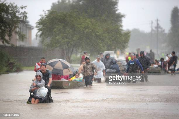 People are rescued from a flooded neighborhood after it was inundated with rain water, remnants of Hurricane Harvey, on August 28, 2017 in Houston,...