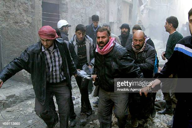 People are rescued from buildings after Syrian army helicopters dropped 'barrel bombs' on December 23 2013 in Aleppo Syria It has been reported that...