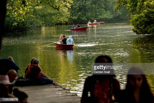 """People are rowing boats in front of the """"Cafe am neue See"""" on the second day that people are no longer required to show a negative Covid test result..."""