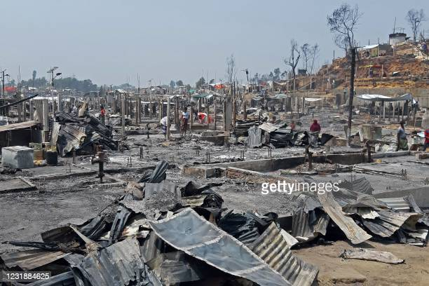 People are seen amidst the debris at a Rohingya refugee camp in Ukhia on March 23, 2021 after a huge blaze forced around 50,000 people to flee.