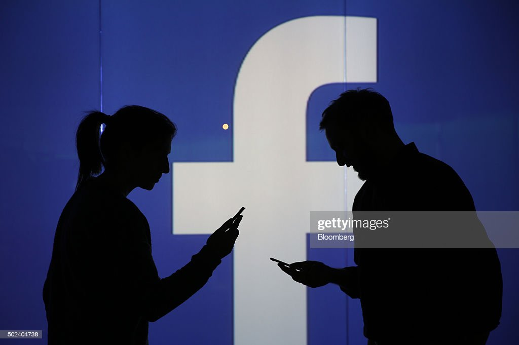 People are seen as silhouettes as they check mobile devices whilst standing against an illuminated wall bearing Facebook Inc.s logo in this arranged photograph in London, U.K., on Wednesday, Dec. 23, 2015. Facebook Inc.s WhatsApp messaging service, with more than 100 million local users, is the most-used app in Brazil, according to an Ibope poll published on Dec. 15. Photographer: Chris Ratcliffe/Bloomberg via Getty Images