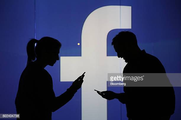 People are seen as silhouettes as they check mobile devices whilst standing against an illuminated wall bearing Facebook Incs logo in this arranged...