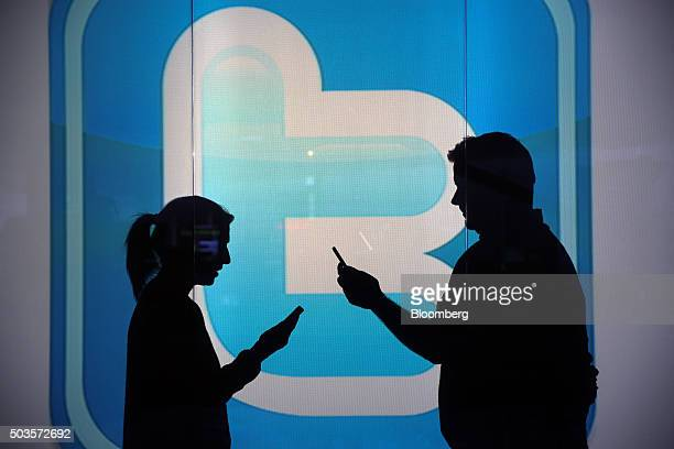People are seen as silhouettes as they check mobile devices whilst standing against an illuminated wall bearing Twitter Inc's logo in this arranged...