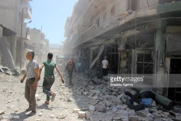 People are seen at a damaged site after airstrikes hit residential areas of Jisr alShughur in the northwestern Idlib province which is part of the...