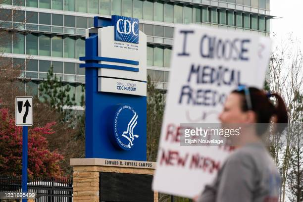 People are seen at a protest against masks, vaccines, and vaccine passports outside the headquarters of the Centers for Disease Control on March 13,...