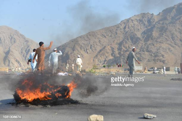 People are seen at site as smoke rises from a burning tyre after a suicide blast ripped through a crowd of protesters in Nanganhar province of...