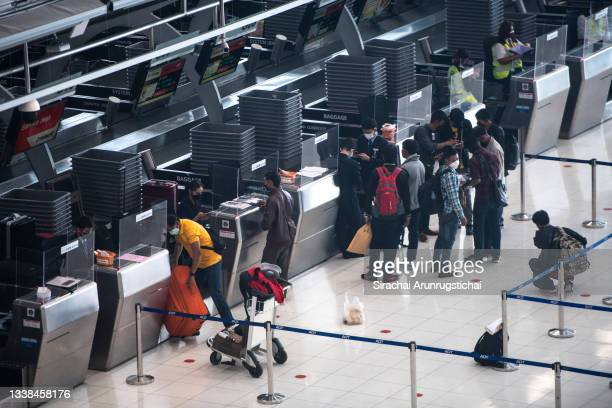 People are seen at the check in counters in the departure hall at Suvarnabhumi Airport on September 05, 2021 in Bangkok, Thailand. With the ease of...