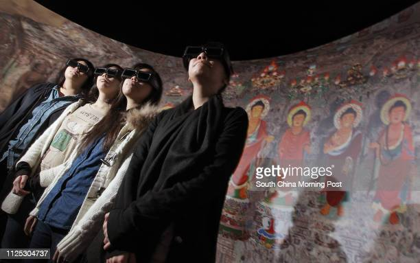 """People are seen at the press preview of """"Pure Land:Inside the Mogao Grottoes at Dunhuang"""" uses 3D effects to let visitors to experience the virtual..."""