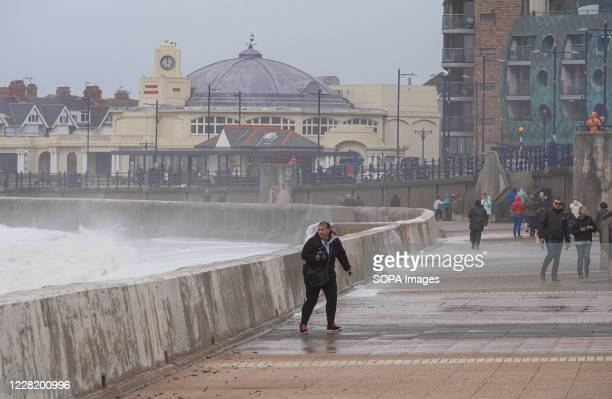 People are seen at the sea wall at Porthcawl South Wales as Storm Francis hits the South Wales Coast.