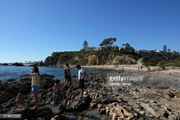 People are seen at the tidal pools at Little Corona Beach on April 15 2020 in Newport Beach California Southern California has seen warmer weather...