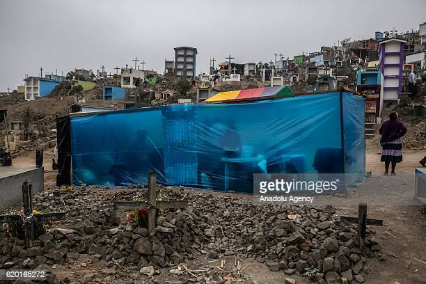 People are seen behind a blue plastic tent where they eat at the Nueva Esperanza cemetery Villa Maria del Triunfo district during the Day of the Dead...