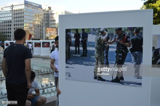 People are seen beside a photo at a photography exhibition to the 1st anniversary of Turkey's failed coup attempt in Ankara Turkey on July 09 as the...