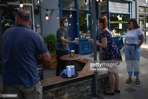 People are seen buying takeaway pints at a pub on Wandsworth Common on May 28 2020 in London, England. The prime minister announced the general...