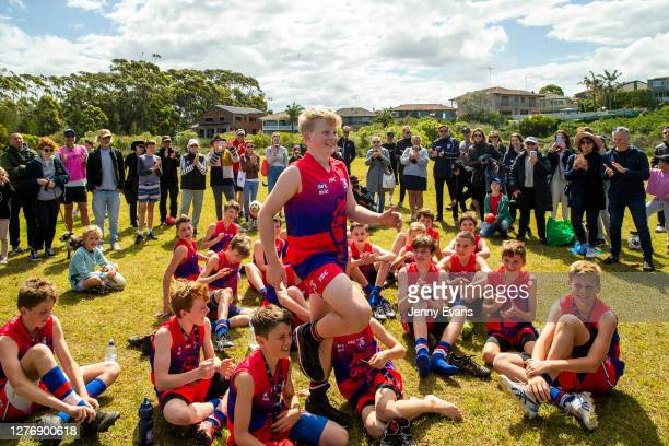 People are seen cheering and taking photos of members of the East Sydney Bulldogs during a medal presentation after their win in the AFL Under 13's...
