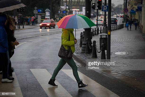People are seen crossing a busy road on a rainy Saturday in Bydgoszcz Poland on November 19 2016