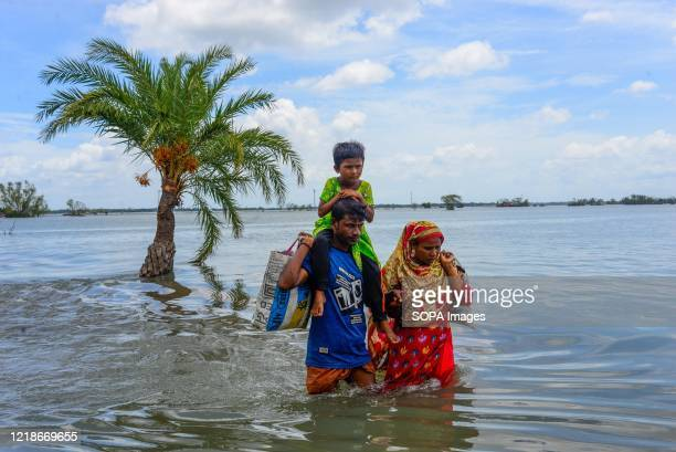 People are seen crossing a flooded road as the embankment of the coastal area was broken after the landfall of cyclone Amphan. Thousands of shrimp...