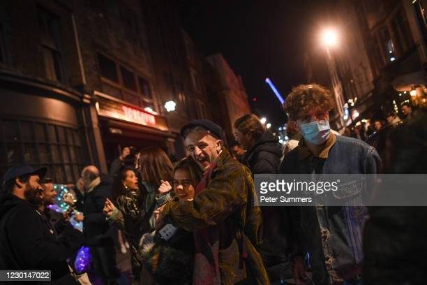 People are seen dancing in the street in Soho, ahead of London being moved into Tier 3 of the pandemic-control system on Wednesday, on December 15,...