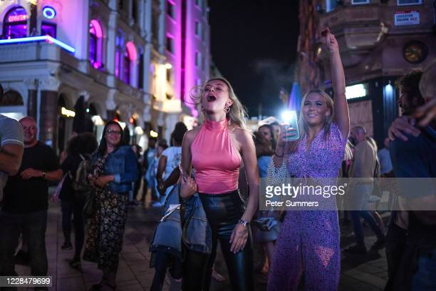 People are seen dancing to a busker in Leicester Square on September 12, 2020 in London, England. From Monday, September 14, groups of more than six...
