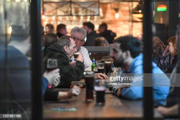 People are seen drinking inside a pub on March 20, 2020 in London, United Kingdom. British Prime Minister Boris Johnson announced that the country's...