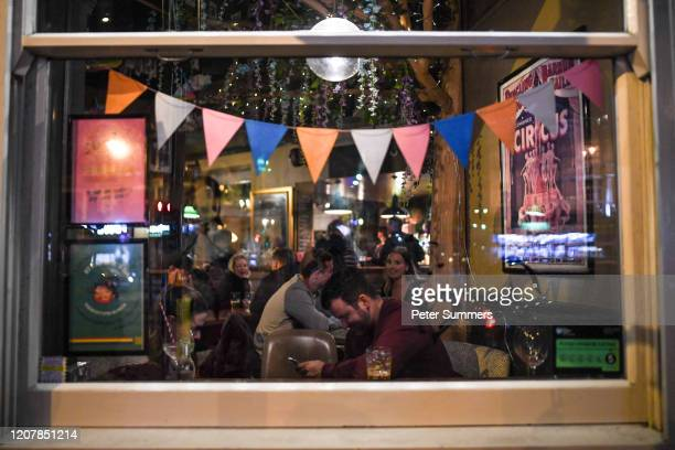 People are seen drinking inside a pub on March 20 2020 in London United Kingdom British Prime Minister Boris Johnson announced that the country's...