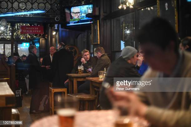 People are seen drinking inside the Red Lion pub on March 20, 2020 in London, United Kingdom. British Prime Minister Boris Johnson announced that the...