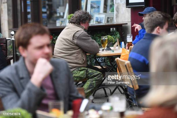 People are seen drinking outside a pub on April 26, 2021 in St Andrews, United Kingdom. Hospitality and non-essential shops have reopened from today...
