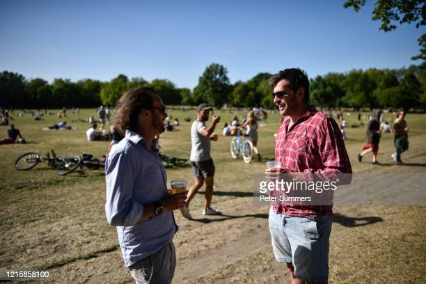 People are seen drinking takeaway pints on Wandsworth Common on May 28 2020 in London England The prime minister announced the general contours of a...