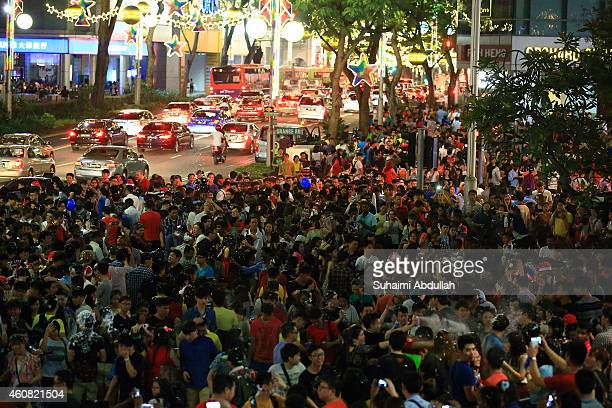People are seen during Christmas eve at Orchard Road on December 24 2014 in Singapore Every year the famous shopping road is decorated with Christmas...