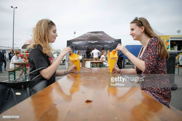 People are seen eating churros with chocolate sauce at a food truck rally in Bydgoszcz Poland on 20 May 2017