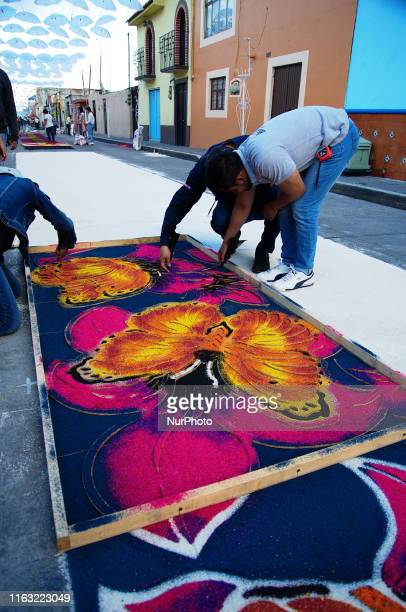 People are seen elaborating a colored sawdust carpets an ephemeral art in honor of the Virgin of Charity on August 14 2019 in Huamantla Mexico...