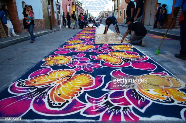 People are seen elaborating a colored sawdust carpets, an ephemeral art in honor of the Virgin of Charity, on August 14, 2019 in Huamantla, Mexico....