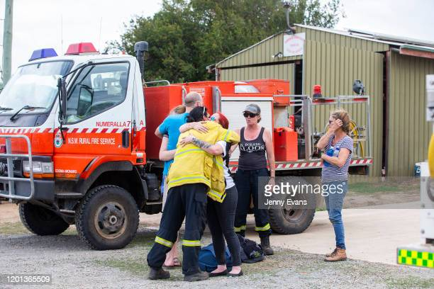 People are seen embracing at Numeralla Rural Fire Brigade near the scene of a water tanker plane crash on January 23, 2020 in Cooma, Australia. Three...