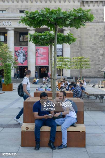 People are seen enjoying the Spring weather in a temporary garden built at the Palace of Culture and Sciences in Warsaw Poland on May 11 2018