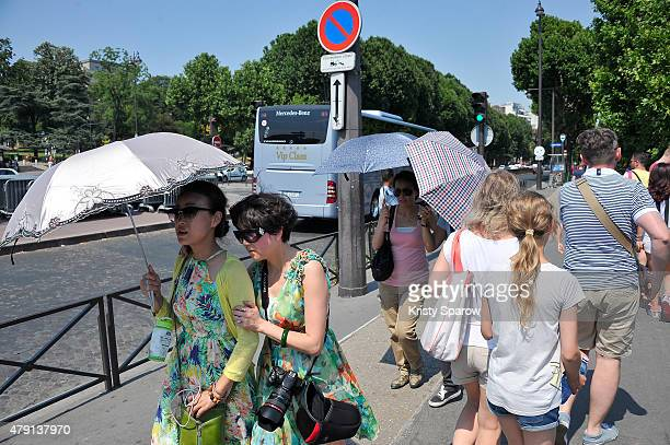 People are seen enjoying the sun at the Eiffel Tower during the heatwave on July 1 2015 in Paris France France is currently experiencing a heatwave...