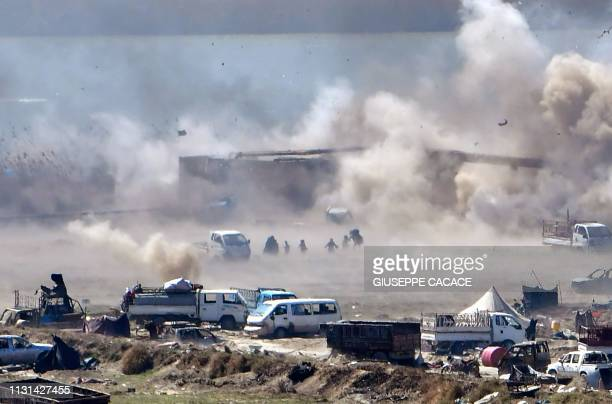 TOPSHOT People are seen fleeing as heavy smoke rises above the Islamic State group's last remaining position in the village of Baghouz during battles...